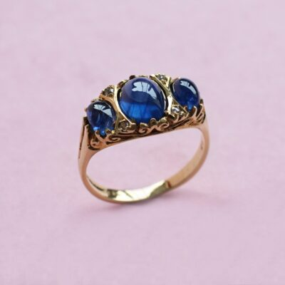 sapphire cabochon three-stone ring with diamond detail