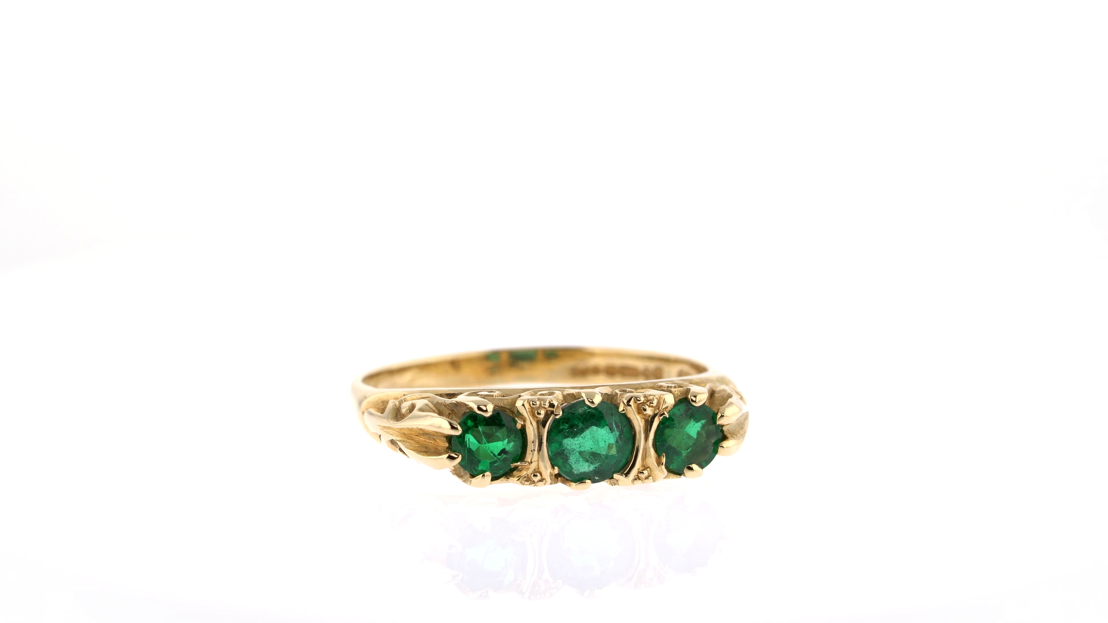 emerald and yellow gold three stone ring
