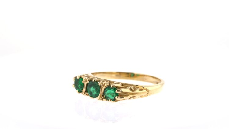 exquisite three-stone emerald ring in yellow gold