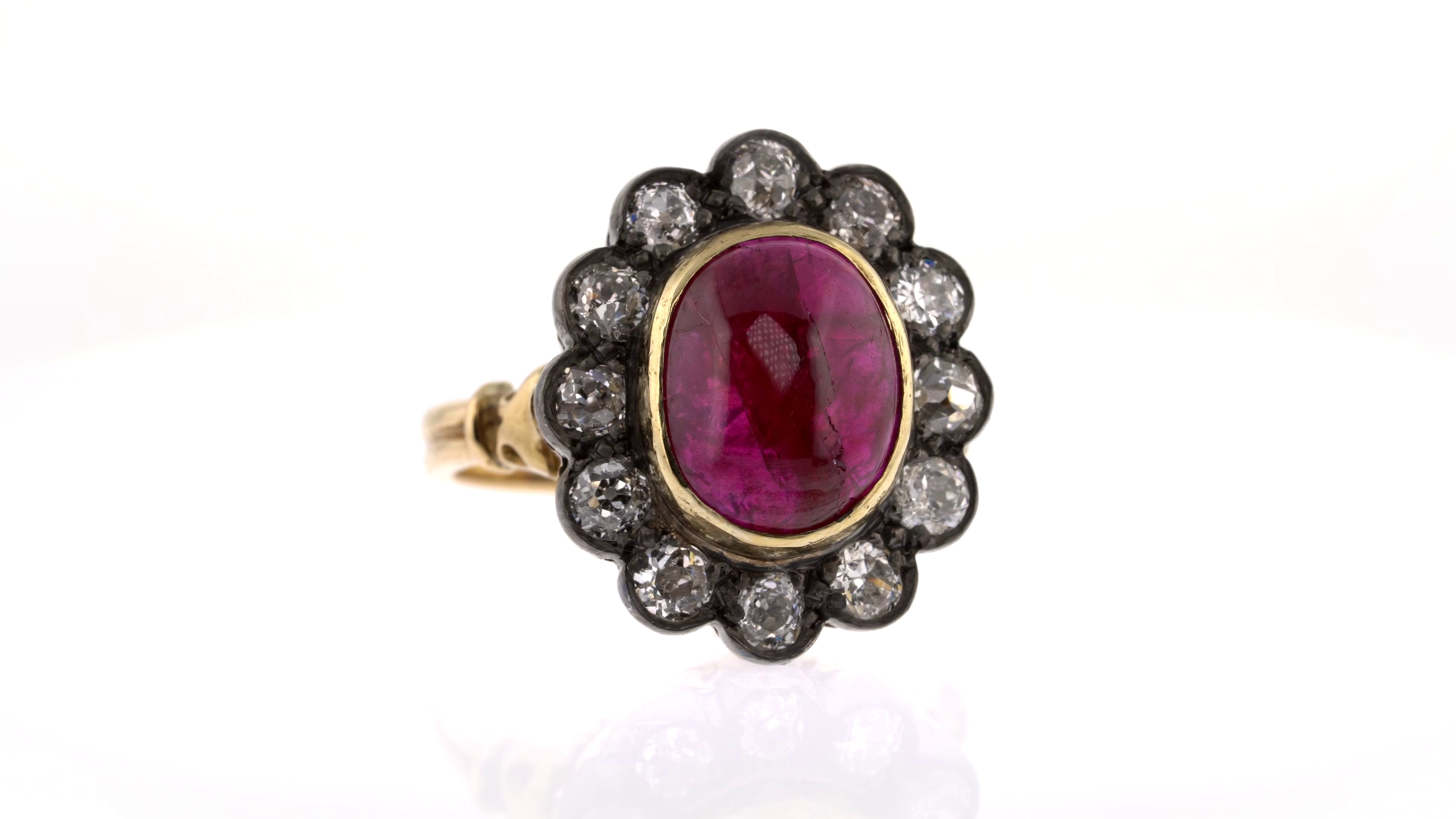 ruby cabochon with white diamond surround ring