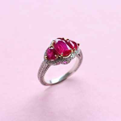 ruby three stone ring with white diamond surround